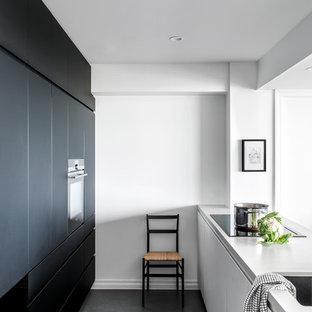 Новый формат декора квартиры: маленькая параллельная кухня-гостиная с врезной раковиной, плоскими фасадами, черными фасадами, столешницей из кварцевого композита, техникой под мебельный фасад, полом из линолеума, серым полом и белой столешницей