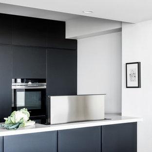 Неиссякаемый источник вдохновения для домашнего уюта: маленькая параллельная кухня-гостиная с врезной раковиной, плоскими фасадами, черными фасадами, столешницей из кварцевого агломерата, техникой под мебельный фасад, полом из линолеума, серым полом и белой столешницей