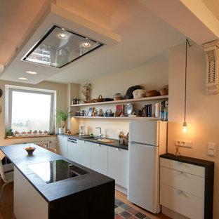 Eklektische Küche mit Doppelwaschbecken, flächenbündigen Schrankfronten, weißen Schränken, Küchenrückwand in Beige, dunklem Holzboden, Kücheninsel und schwarzer Arbeitsplatte in Essen