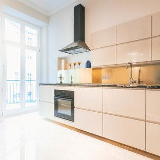 ベルリンの大きいエクレクティックスタイルのおしゃれなキッチン (ドロップインシンク、フラットパネル扉のキャビネット、ベージュのキャビネット、御影石カウンター、メタリックのキッチンパネル、メタルタイルのキッチンパネル、黒い調理設備、大理石の床、ベージュの床) の写真
