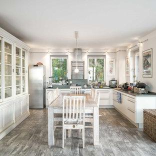 Offene, Große Mediterrane Küche ohne Insel in U-Form mit flächenbündigen Schrankfronten, weißen Schränken, Küchengeräten aus Edelstahl, beigem Boden und grauer Arbeitsplatte in Sonstige
