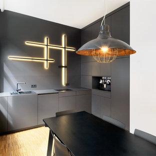 Kleine Industrial Küche mit Einbauwaschbecken, flächenbündigen Schrankfronten, schwarzen Schränken, Küchenrückwand in Schwarz und braunem Holzboden in Nürnberg