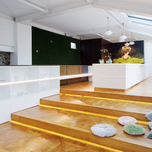 Design ideas for a large asian single-wall open plan kitchen in Leipzig with a drop-in sink, raised-panel cabinets, white cabinets, white splashback, window splashback, stainless steel appliances, light hardwood floors, with island, beige floor, white benchtop and solid surface benchtops.