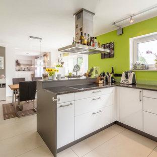 Offene, Mittelgroße Moderne Küche in L-Form mit flächenbündigen Schrankfronten, weißen Schränken, Küchenrückwand in Grün, Halbinsel, beigem Boden und schwarzer Arbeitsplatte in Sonstige