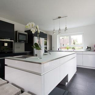 Modelo de cocina en L, contemporánea, abierta, con armarios con paneles lisos, puertas de armario blancas, encimera de vidrio, salpicadero blanco, electrodomésticos de colores y una isla