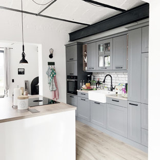 Inspiration for a large contemporary single-wall open plan kitchen in Berlin with a belfast sink, raised-panel cabinets, grey cabinets, soapstone worktops, white splashback, brick splashback, light hardwood flooring, multiple islands, beige worktops and a vaulted ceiling.