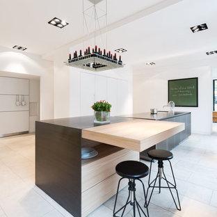 Idéer för mycket stora funkis linjära kök med öppen planlösning, med släta luckor, vita skåp, bänkskiva i rostfritt stål, flera köksöar, en integrerad diskho och kalkstensgolv