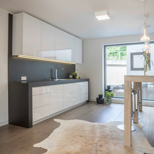 Offene, Einzeilige, Kleine Moderne Küche ohne Insel mit Einbauwaschbecken, flächenbündigen Schrankfronten, weißen Schränken, Küchenrückwand in Grau, braunem Holzboden und braunem Boden in Essen