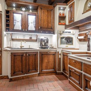 他の地域の中サイズの地中海スタイルのおしゃれなキッチン (ドロップインシンク、濃色木目調キャビネット、タイルカウンター、ベージュキッチンパネル、トラバーチンの床、白い調理設備、アイランドなし、赤い床、ベージュのキッチンカウンター) の写真