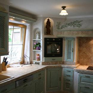 Esempio di una grande cucina mediterranea con lavello da incasso, ante a filo, ante turchesi, paraspruzzi beige, paraspruzzi con piastrelle a mosaico, elettrodomestici neri, pavimento in terracotta, nessuna isola, pavimento beige e top beige