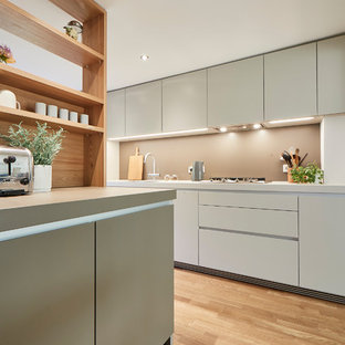Inspiration for a mid-sized contemporary single-wall open plan kitchen in Hamburg with a drop-in sink, flat-panel cabinets, beige splashback, light hardwood floors, beige floor, beige cabinets, laminate benchtops, stainless steel appliances, a peninsula and beige benchtop.