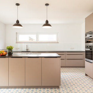 Inspiration for a large contemporary l-shaped open plan kitchen in Frankfurt with a single-bowl sink, beaded inset cabinets, beige cabinets, white splashback, glass sheet splashback, terra-cotta floors, with island, multi-coloured floor, panelled appliances and black benchtop.