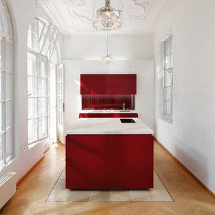Geschlossene, Mittelgroße Klassische Küche mit Unterbauwaschbecken, flächenbündigen Schrankfronten, roten Schränken, Küchenrückwand in Rot, Glasrückwand, Elektrogeräten mit Frontblende, hellem Holzboden und Kücheninsel in München