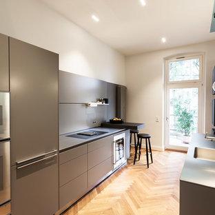 Geschlossene, Zweizeilige, Mittelgroße Moderne Küche ohne Insel mit integriertem Waschbecken, flächenbündigen Schrankfronten, grauen Schränken, Küchenrückwand in Grau, Küchengeräten aus Edelstahl, braunem Holzboden, braunem Boden und grauer Arbeitsplatte in Düsseldorf