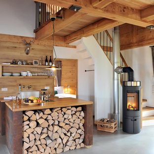 Foto de cocina lineal, rural, de tamaño medio, abierta, con fregadero sobremueble, suelo de cemento, una isla, encimera de madera, armarios abiertos y puertas de armario de madera oscura