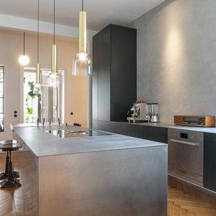 Zweizeilige Moderne Küche mit Unterbauwaschbecken, flächenbündigen Schrankfronten, schwarzen Schränken, Küchengeräten aus Edelstahl, braunem Holzboden, Kücheninsel, braunem Boden und grauer Arbeitsplatte in Berlin