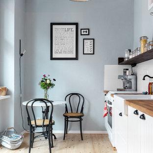 Einzeilige, Kleine Nordische Wohnküche ohne Insel mit Landhausspüle, weißen Schränken, Arbeitsplatte aus Holz, Küchenrückwand in Weiß, hellem Holzboden, Schrankfronten mit vertiefter Füllung, weißen Elektrogeräten und Rückwand aus Keramikfliesen in Berlin