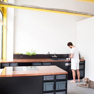 Aménagement d'une cuisine ouverte linéaire industrielle de taille moyenne avec un évier posé, des portes de placard noires, un plan de travail en cuivre, une crédence blanche, un électroménager noir, béton au sol et un îlot central.