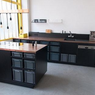 ベルリンの中くらいのインダストリアルスタイルのおしゃれなキッチン (ドロップインシンク、黒いキャビネット、銅製カウンター、白いキッチンパネル、黒い調理設備、コンクリートの床) の写真