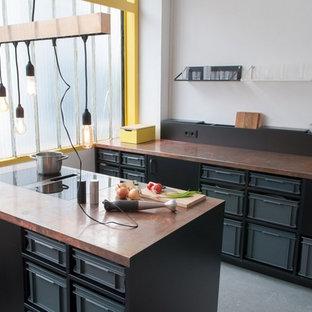 Offene, Einzeilige, Mittelgroße Moderne Küche mit Einbauwaschbecken, schwarzen Schränken, Kupfer-Arbeitsplatte, Küchenrückwand in Weiß, schwarzen Elektrogeräten, Betonboden und Kücheninsel in Berlin