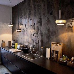 Foto di una cucina lineare contemporanea di medie dimensioni con ante nere, paraspruzzi nero, lavello da incasso, ante lisce e pavimento in legno massello medio