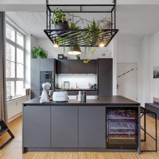Zweizeilige Stilmix Küche mit flächenbündigen Schrankfronten, grauen Schränken, schwarzen Elektrogeräten, braunem Holzboden, Kücheninsel, braunem Boden und schwarzer Arbeitsplatte in Frankfurt am Main