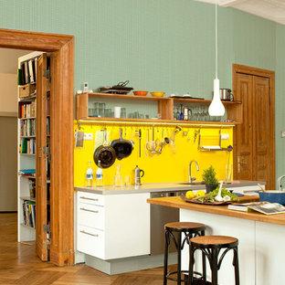 Foto på ett stort eklektiskt kök med öppen planlösning, med släta luckor, vita skåp, gult stänkskydd, rostfria vitvaror, mellanmörkt trägolv, en köksö, en integrerad diskho och bänkskiva i rostfritt stål