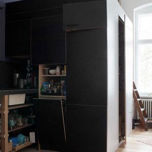 Inspiration för mellanstora moderna linjära svart kök med öppen planlösning, med en nedsänkt diskho, släta luckor, svarta skåp, kaklad bänkskiva, blått stänkskydd, integrerade vitvaror och ljust trägolv