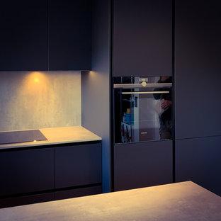 На фото: маленькая п-образная кухня-гостиная в стиле модернизм с накладной раковиной, плоскими фасадами, черными фасадами, столешницей из ламината, серым фартуком, черной техникой, светлым паркетным полом, полуостровом и зеленой столешницей с