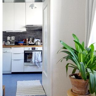ベルリンの中サイズの北欧スタイルのおしゃれなキッチン (シングルシンク、フラットパネル扉のキャビネット、白いキャビネット、木材カウンター、グレーのキッチンパネル、シルバーの調理設備の、リノリウムの床、アイランドなし、スレートの床、青い床) の写真