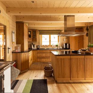 ライプツィヒの大きいカントリー風おしゃれなキッチン (中間色木目調キャビネット、無垢フローリング、ドロップインシンク、茶色いキッチンパネル、パネルと同色の調理設備) の写真