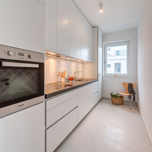 Photo of a small contemporary single-wall enclosed kitchen in Cologne with a built-in sink, flat-panel cabinets, white cabinets, granite worktops, stainless steel appliances, cement flooring, no island and beige floors.