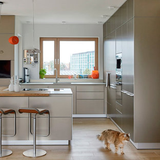 Design ideas for a mid-sized contemporary l-shaped eat-in kitchen in Hanover with a single-bowl sink, flat-panel cabinets, concrete benchtops, black appliances, medium hardwood floors, brown floor, brown cabinets and a peninsula.