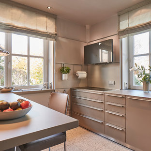 ハンブルクの大きいコンテンポラリースタイルのおしゃれなキッチン (一体型シンク、フラットパネル扉のキャビネット、グレーのキャビネット、木材カウンター、ベージュキッチンパネル、木材のキッチンパネル、シルバーの調理設備の、テラゾの床、ベージュの床、ベージュのキッチンカウンター) の写真