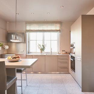 Große Moderne Wohnküche in L-Form mit flächenbündigen Schrankfronten, grauen Schränken, Küchenrückwand in Beige, Küchengeräten aus Edelstahl, Terrazzo-Boden, Halbinsel, beigem Boden, beiger Arbeitsplatte und Unterbauwaschbecken in Hamburg