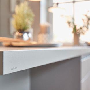 Ejemplo de cocina en L, contemporánea, grande, abierta, con fregadero integrado, armarios con paneles lisos, puertas de armario grises, encimera de madera, salpicadero beige, salpicadero de madera, electrodomésticos de acero inoxidable, suelo de terrazo, península, suelo beige y encimeras beige