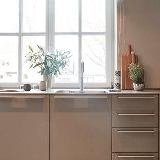 Ejemplo de cocina en L, actual, grande, abierta, con fregadero integrado, armarios con paneles lisos, puertas de armario grises, encimera de madera, salpicadero beige, salpicadero de madera, electrodomésticos de acero inoxidable, suelo de terrazo, península, suelo beige y encimeras beige