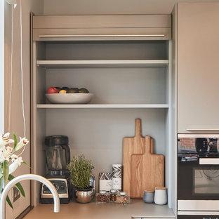 ハンブルクの大きいコンテンポラリースタイルのおしゃれなキッチン (一体型シンク、フラットパネル扉のキャビネット、グレーのキャビネット、木材カウンター、ベージュキッチンパネル、木材のキッチンパネル、シルバーの調理設備の、テラゾーの床、ベージュの床、ベージュのキッチンカウンター) の写真