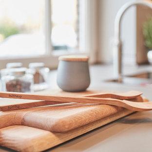ハンブルクの広いコンテンポラリースタイルのおしゃれなキッチン (一体型シンク、フラットパネル扉のキャビネット、グレーのキャビネット、木材カウンター、ベージュキッチンパネル、木材のキッチンパネル、シルバーの調理設備、テラゾーの床、ベージュの床、ベージュのキッチンカウンター) の写真