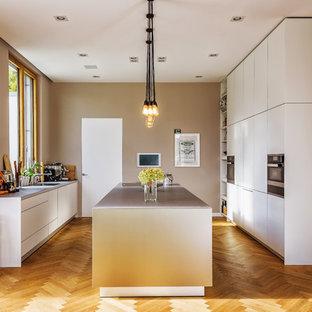 Offene, Große Moderne Küche in U-Form mit flächenbündigen Schrankfronten, beigen Schränken, Edelstahl-Arbeitsplatte, braunem Holzboden, Kücheninsel, braunem Boden, grauer Arbeitsplatte, Unterbauwaschbecken und schwarzen Elektrogeräten in Berlin