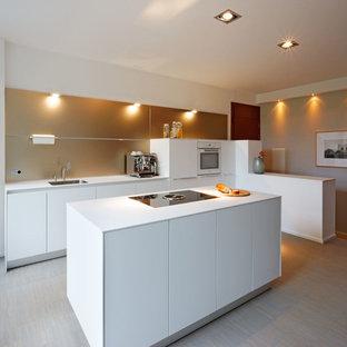 Zweizeilige, Offene, Mittelgroße Moderne Küche mit flächenbündigen Schrankfronten, weißen Schränken, Laminat-Arbeitsplatte, Küchenrückwand in Beige, Kücheninsel, Unterbauwaschbecken und hellem Holzboden in Düsseldorf