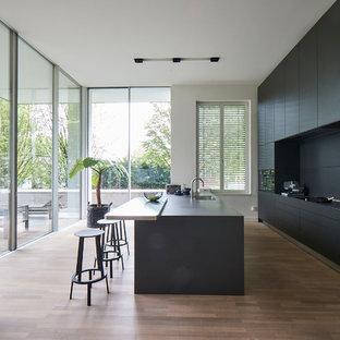 Große, Zweizeilige Moderne Wohnküche mit flächenbündigen Schrankfronten, schwarzen Schränken, Küchenrückwand in Schwarz, schwarzen Elektrogeräten, Kücheninsel, schwarzer Arbeitsplatte, Waschbecken, Betonarbeitsplatte, braunem Holzboden und braunem Boden in Hamburg
