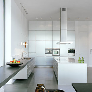 This is an example of a large contemporary l-shaped kitchen/diner in Cologne with a built-in sink, flat-panel cabinets, white cabinets, glass worktops, stainless steel appliances, vinyl flooring, multiple islands and grey floors.
