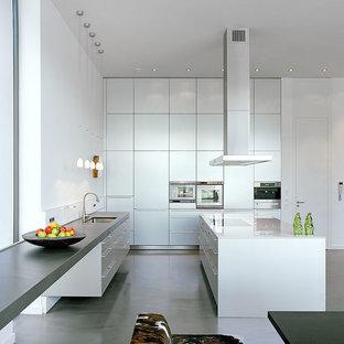 Große Moderne Wohnküche in L-Form mit Einbauwaschbecken, flächenbündigen Schrankfronten, weißen Schränken, Glas-Arbeitsplatte, Küchengeräten aus Edelstahl, Vinylboden, zwei Kücheninseln und grauem Boden in Köln