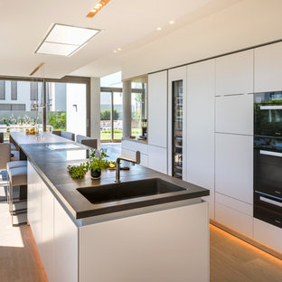 Zweizeilige, Große Moderne Wohnküche mit integriertem Waschbecken, flächenbündigen Schrankfronten, weißen Schränken, Betonarbeitsplatte, schwarzen Elektrogeräten, braunem Holzboden, zwei Kücheninseln und braunem Boden in Köln
