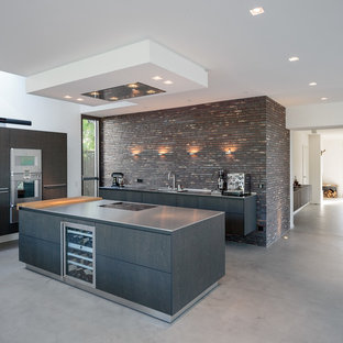 Large industrial l-shaped open plan kitchen in Cologne with a drop-in sink, flat-panel cabinets, dark wood cabinets, brown splashback, brick splashback, stainless steel appliances, vinyl floors, multiple islands and grey floor.