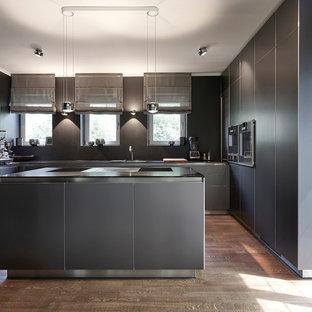 Geschlossene, Mittelgroße Moderne Küche in U-Form mit flächenbündigen Schrankfronten, schwarzen Schränken, Küchenrückwand in Schwarz, schwarzen Elektrogeräten, braunem Holzboden, Kücheninsel, braunem Boden und schwarzer Arbeitsplatte in München