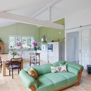 Moderne Wohnküche in L-Form mit weißen Schränken, Küchengeräten aus Edelstahl, Laminat, braunem Boden und grauer Arbeitsplatte in Berlin