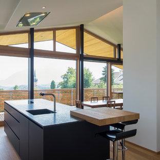 Immagine di una cucina moderna con lavello sottopiano, ante lisce, ante nere, elettrodomestici da incasso, pavimento in legno massello medio, isola, pavimento marrone e top nero