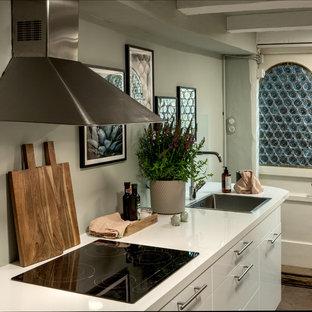 Lantlig inredning av ett avskilt, litet vit linjärt vitt kök, med en integrerad diskho, släta luckor, vita skåp, laminatbänkskiva, grönt stänkskydd, rostfria vitvaror, tegelgolv och brunt golv